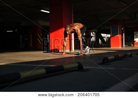 Portrait of a fit strong half naked african sportsman getting ready to start running indoors