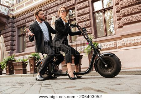 Full length side view image of Displeased bearded business man sitting on modern motorbike outdoors with young elegant woman which looking at mirror