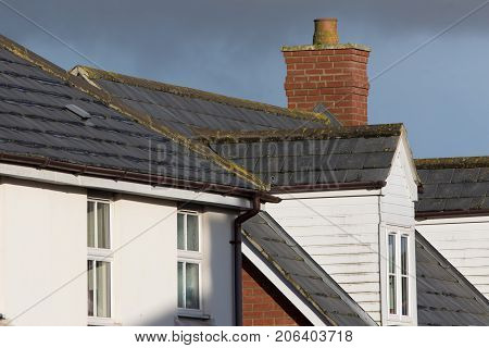 Modern town house roof with slate tiles chimney and dormer with white pvc window and wood cladding. Brown guttering.