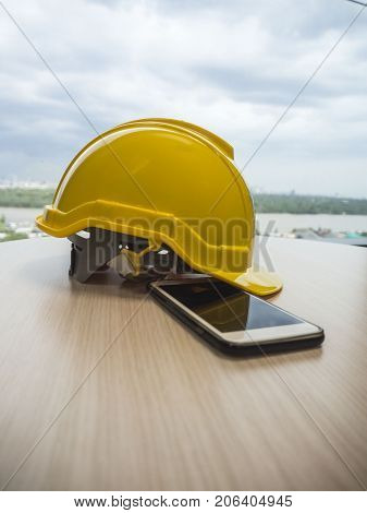 The yellow safety helmet with smartphone on the wood table inside window concept security and protection
