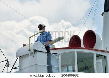 Lucerne Switzerland - June 14 2017: Captain of a vintage steamer on the control deck in the port of Lucerne