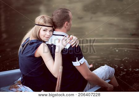 sweet guy and girl sitting on the edge of boat, beautiful couple having fun in a boat outdoors, happy teenager have fun in a boat on the lake