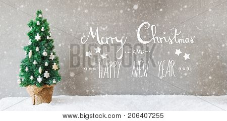 Calligraphy With English Text Merry Christmas And Happy New Year. Christmas Tree With Silver Christmas Ball Ornament On Snow With Snowflakes.
