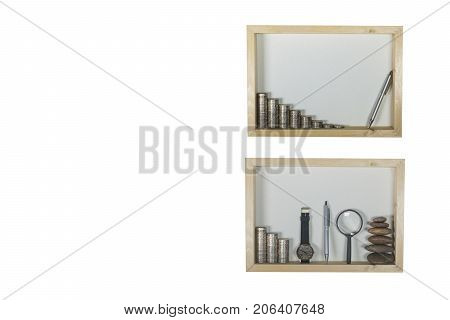 stack coin pen magnifying glass and watch in wooden frame isolated on white wall background. Financial and saving concept and copy space.