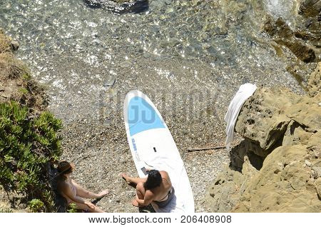 CADAQUES, SPAIN - JULY 27, 2017: Women at a small cove seen from above in Cadaques Girona Catalonia Spain.