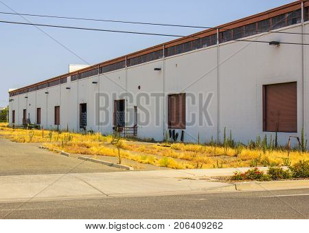 Abandoned Commercial Building With Loading Docks & Overgrown Weeds