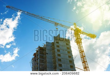 Silhouette construction crane equipment, Industrial construction cranes and building over amazing sunset sky abstract background, dramatic clouds behind crane in the evening.