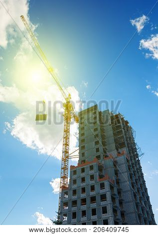 Hoisting cranes working building construction on bright blue sky and big cloud with sun flare background.