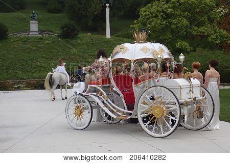 Princess riding a white horse and a coach with a retinue