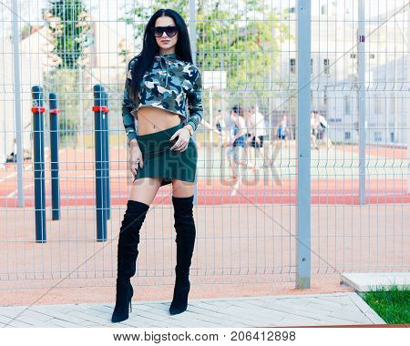 Camouflage. Fashion on the street. Beautiful brunette girl in short skirt khaki high black high heeled boots and super fashionable sunglasses.