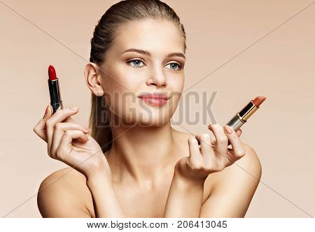 Attractive young girl with lipstick. Photo of blonde girl with red and beige pomade on beige background. Youth and skin care concept