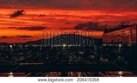 Stunning sunset on huge railroad terminal with multiple railway tracks glass facade on the right and hills ridge in distance; reddish sky autumn evening many reflections and lights Adler Russia