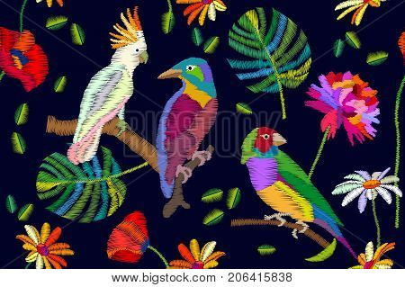 Seamless vector pattern with parrots, flowers and palm leaves on black background. Stylized embroidered texture. Vintage motifs.