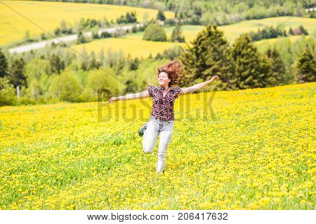 Young Woman Running, Jumping In Air And Smiling On Countryside Yellow Dandelion Flower Fields In Sum