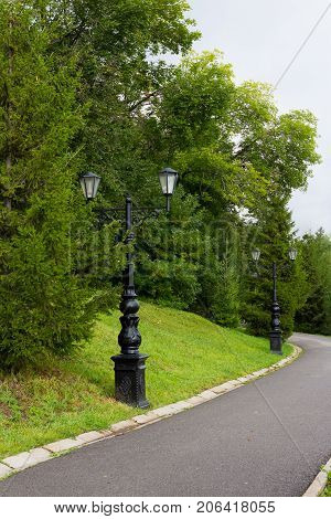 Street lamp in the old style with two lamps of wrought iron with curls on the long leg Black lamppost and chandelier body, light glass of plafonds. russia