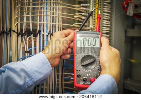 An electrician with multimeter close-up. Hands of service engineer with measuring instrument macro