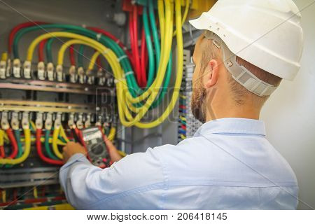 electrician engineer measures voltage of electrical power cables in cabinet. worker in white helmet with multimeter.