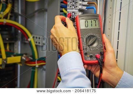 Multimeter in hands of electrician. Engineer adjust electric panel