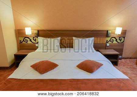 Tween bed in a hotel room illuminated by romantic lamps
