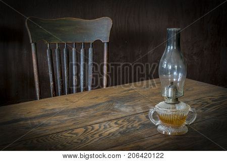 vintage oil lamp on a dusty wooden table with a chair in a dark room
