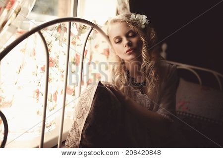 Young Beautiful Blonde In The Bed At Morning Time Near Window Under Sun Rays With Flower In The Hair