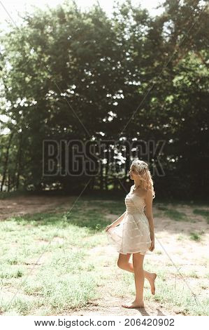 Beautiful Young Woman With Long Curly Blonde Hair Dressed In Boho Style White Dress Posing Near Hove