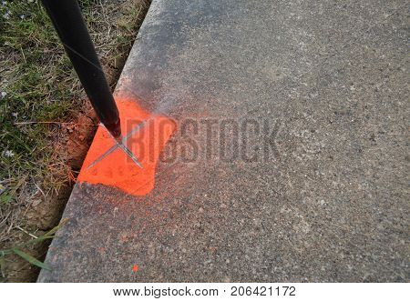 Orange spray paint is used on the sidewalk to mark equipment placement for surveyors.