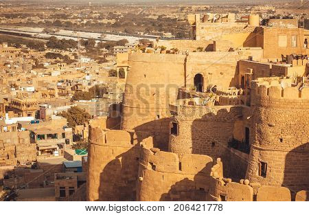 Round towers of historical Jaisalmer fort with monumental stone walls over the old city in Rajasthan, India.