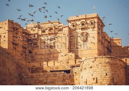 Birds flying over the towers of historical Jaisalmer fort with monumental stone walls in the old city of Rajasthan, India.