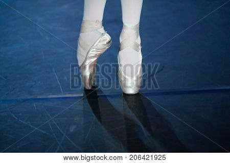 choreography, dancing, outfit concept. pointe shoes of light pink tender color hold on tight little delicate feet of young ballerina and elastic ribbons wrap her ankles