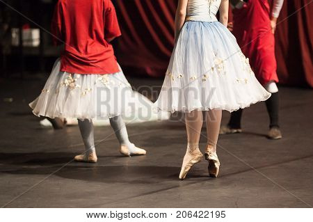 dancing, rehearsal, backstage concept. group of ballet dancers stretching before the concert and one of the ballerinas still wearing grey leg warmers and large bright red sweatshirt