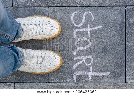 Female legs shod in white sneakers and the word start
