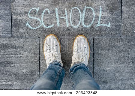 The word school on the asphalt and the feet of the student. Back to school