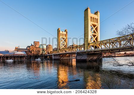 Gold Tower Bridge In Sacramento California During Blue Sunset With Downtown And Goose On Floating Lo