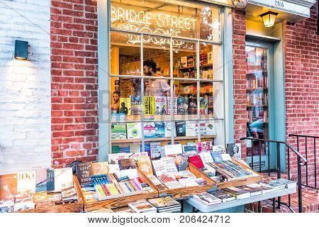 Washington DC USA - August 4 2017: Closeup stack of many used books at independent bookstore in Georgetown neighborhood on sidewalk in downtown during evening