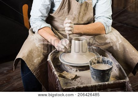 pottery, workshop tools, ceramics art concept - man hands work with potter's wheel, the fingers form the shape of raw fireclay, male master sculpt a utensils with stack, profile and sponge, top view