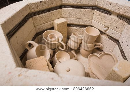 pottery, workshop, ceramics art concept - top view of electric oven for further roasting of unfinished clay products, kiln for cups and unbaked jugs, close