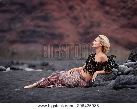 young sensual woman posing on volcanic beach in summer