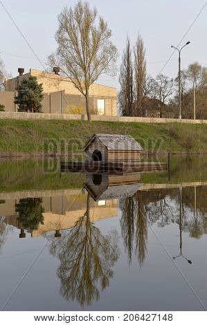 House on the water water flows and the house stands mirror reflection in the river a small house is a good shelter for birds tall trees in the river valley water calms the soul of a person and a good shelter gives confidence on the river there is a cabin
