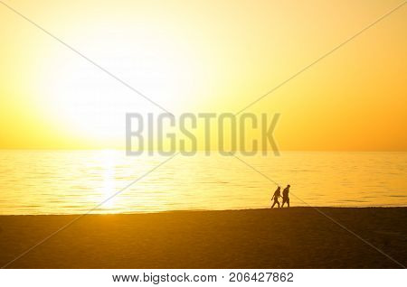 couple of young people walking at sunset on the beach