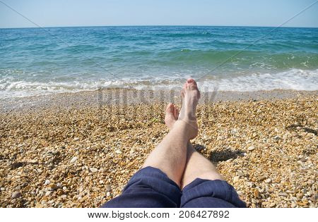 men's feet on the background of sea beach. A vacation at a seaside resort