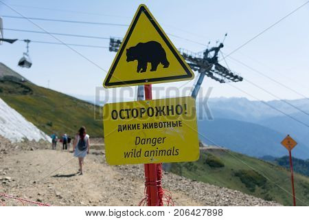 A sign with a warning about wild animals in the mountains in Russian and English
