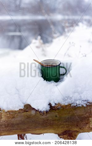 hot tea in cold winter.a Cup of tea on a winter river