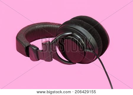 Stereo Headphones In Hand. On Pink Background