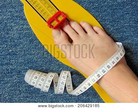 yellow foot measurement device with naked foot upon with measuring tape