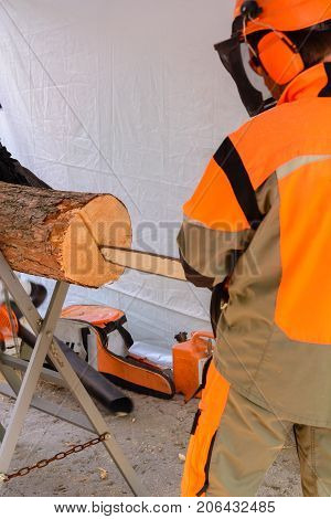 A man saws a large log with a chainsaw. Orange clothes and a light awning. repair or construction