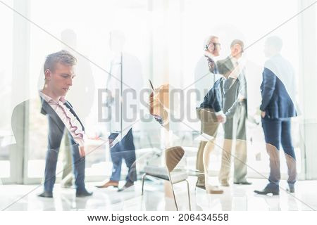 Business communication concept. Businessmen using smart phone while sitting and waiting in office building lobby. Business people talking in background. Double exposure collage image.