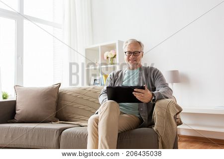 technology, old age, people and lifestyle concept - happy smiling senior man with tablet pc computer sitting on sofa at home