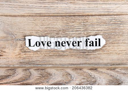 Love never fail text on paper. Word Love never fail on torn paper. Concept Image.