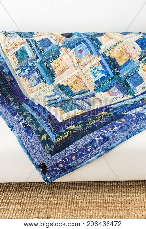 sewing, interior, patchwork, garment industry concept - magnificent blanket in light and dark blue shades, sewed of satin rags with absolutly different design, is laying on the sofa